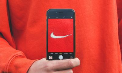 Nike tick on iPhone wit a red sweater background