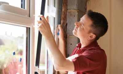 Man in red shirt fitting new double-glazed window