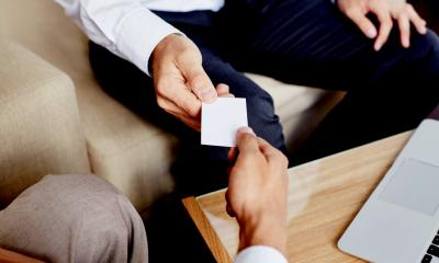 Male hand holding blank business card to another male hand