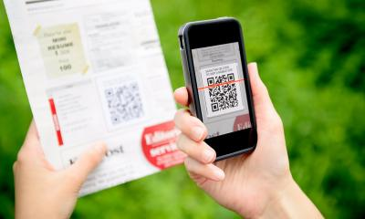 A woman scans a marketing QR code with her smartphone
