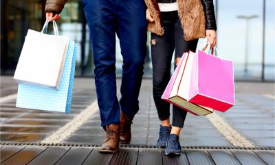 A couple come home from a high street shopping trip with bags full of purchases.