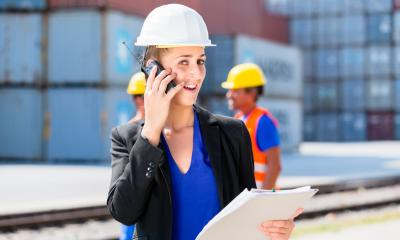 Woman in hard hat on mobile phone at distribution centre