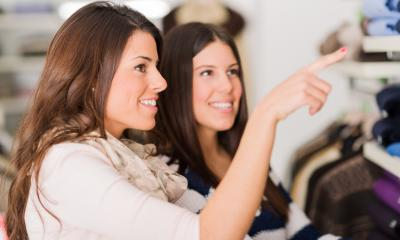 Two women browse the clothes rails in a shop.