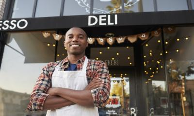 A male restaurant owner stands outside his successful business - strong brand concept.
