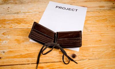 Brown leather wallet on a white piece of paper that says 'PROJECT'