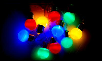 A group of coloured light bulbs in the dark