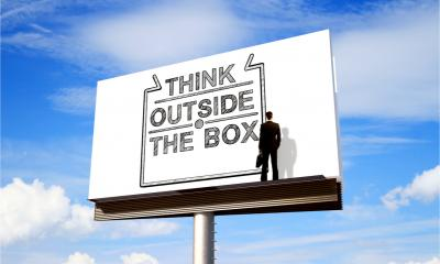 "A billboard shows the words ""Think outside the box"" while a businessman looks on."