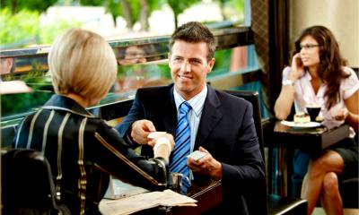 A businessman hands over his business card to a potential client or customer.