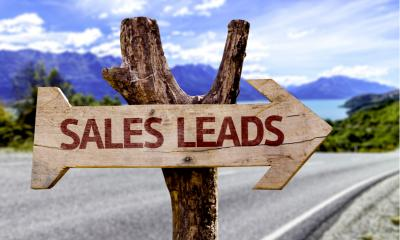 'SALES LEADS' printed on a wooden arrow pointing right